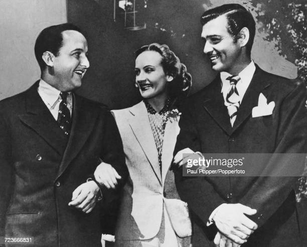 American film actress Carole Lombard poses with her husband Clark Gable right and Gable's press agent Otto Winkler in Los Angeles circa 1941 Both...