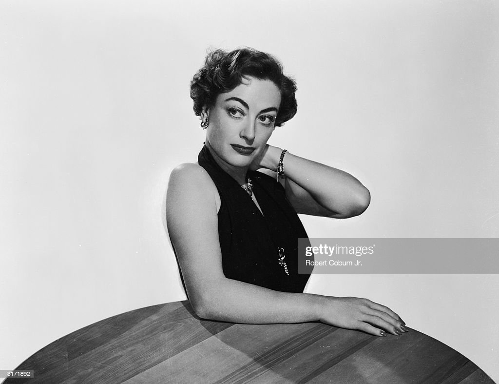 American film actress Joan Crawford leaning on a table in a promotional picture for her latest film 'Harriet Craig'