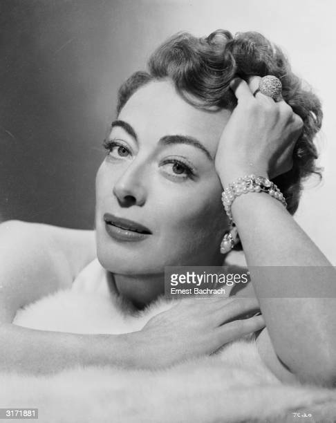 American film actress Joan Crawford lying on a fur rug in a promotional picture for her latest film 'Sudden Fear'