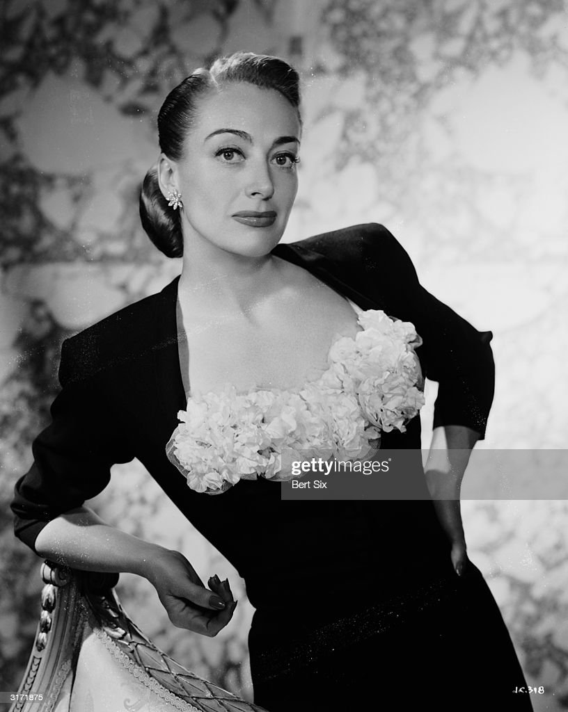 American film actress Joan Crawford wearing a black cocktail dress with a ruched insert