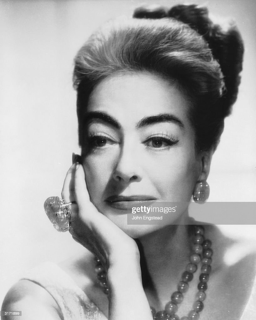 American film actress Joan Crawford wearing an extravagantly large ring and a bead necklace and matching earrings
