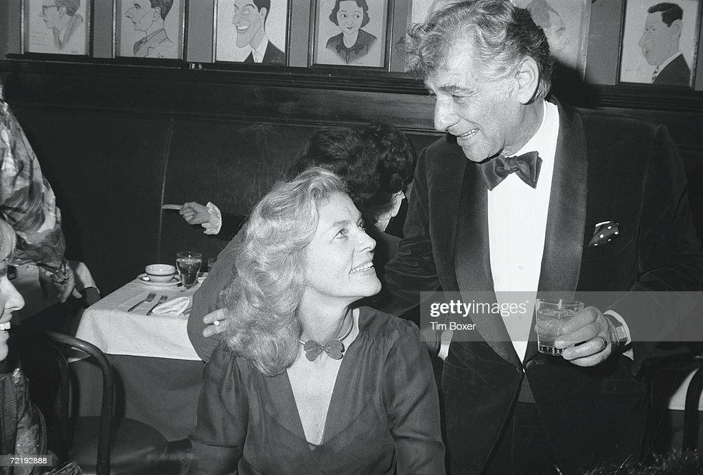 American film actress Lauren Bacall sits and listens as orchestra conductor Leonard Bernstein (1918 - 1990) talks at Sardi's restaurant, Manhattan, New York, 1971.