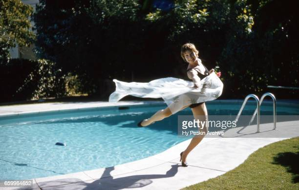 American film and television actress Shirley MacLaine poses for a portrait during a portrait session next to a swimming pool circa 1958