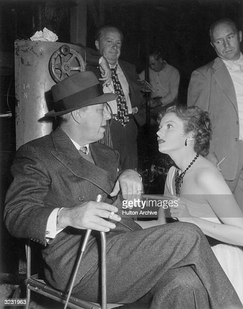 American film director Alexander Hall sits in a chair talking to American actor Rhonda Fleming who kneels by his side on the set of Hall's film 'The...