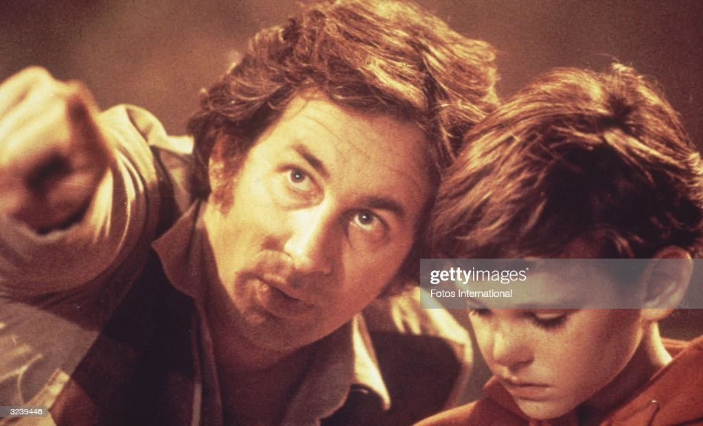 American film director and producer Steven Spielberg points to something in the distance as he directs American actor Henry Thomas in a scene on the...