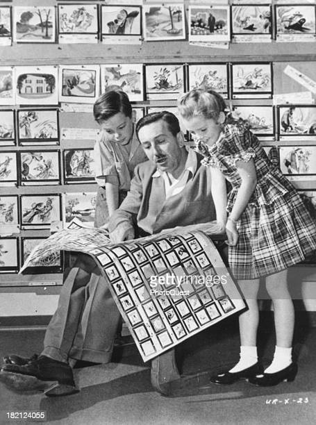American film director animator and businessman Walt Disney shows the storyboards for 'Song of the South' to the film's two child actors Bobby...