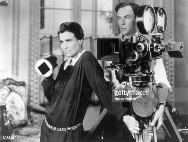 American film director Dorothy Arzner and Alfred Gilks her cinematographer survey a scene as they stand by a camera on the set of her film 'Get Your...