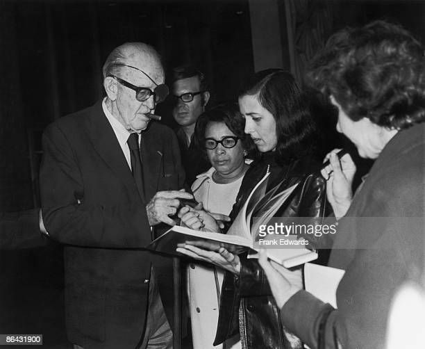 American film director John Ford signs autographs for a group of fans circa 1965