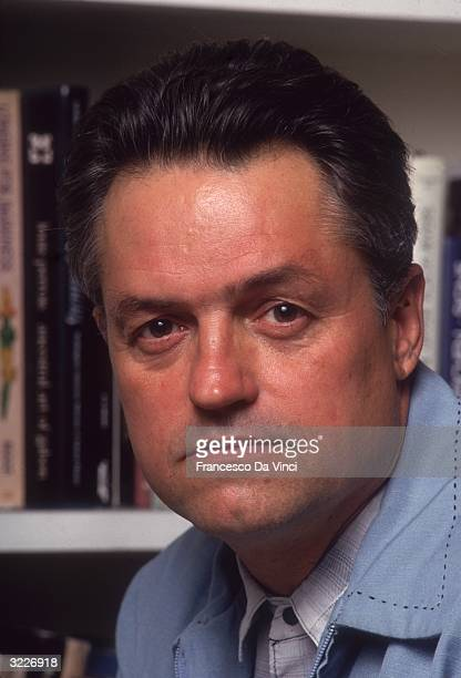 American film director Jonathan Demme posing in front of a bookcase