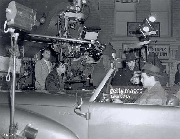 American film director Mervyn LeRoy crouches down next to a convertible automobile as he directs American actors Robert Taylor Lana Turner and Robert...