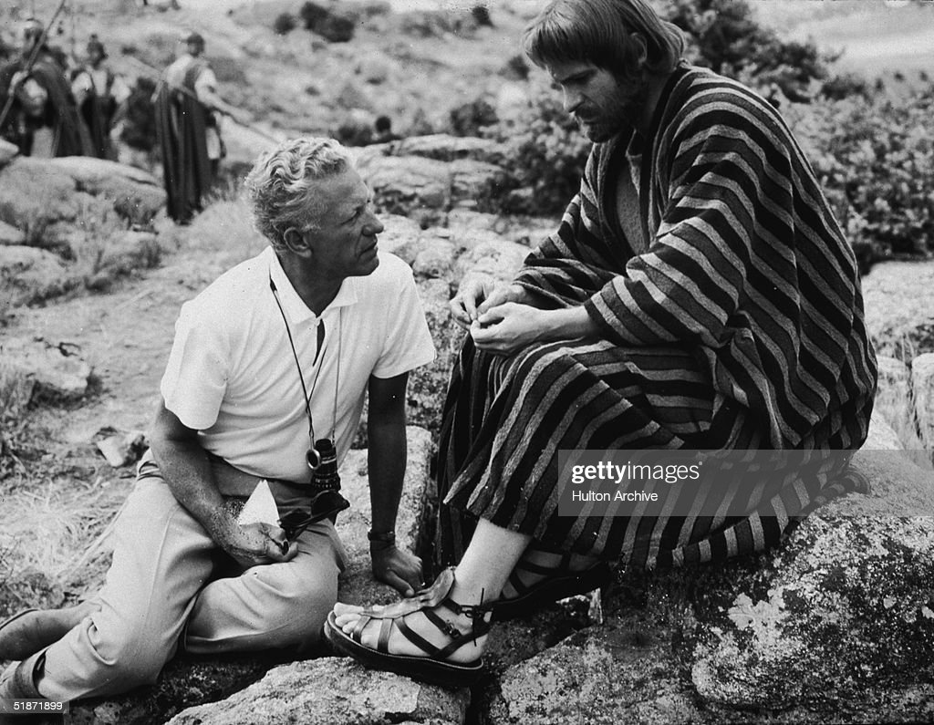 American film director Nicholas Ray (1911 - 1979) (left) and American actor Rip Torn, in costume as Judas Iscariot, discuss a scene on the location of the film 'King of Kings,' Spain, 1961.