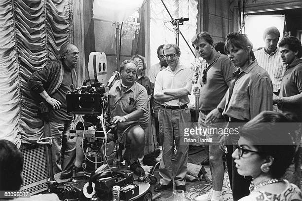American film director Woody Allen stands among his crew and smiles during the filming of a scene from his movie 'Annie Hall' late 1970s