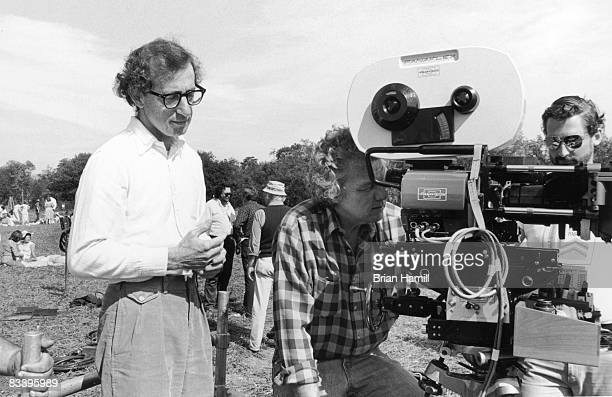 American film director Woody Allen stands behind cinematographer Gordon Willis who looks through a camera viewfinder during the filming of the movie...