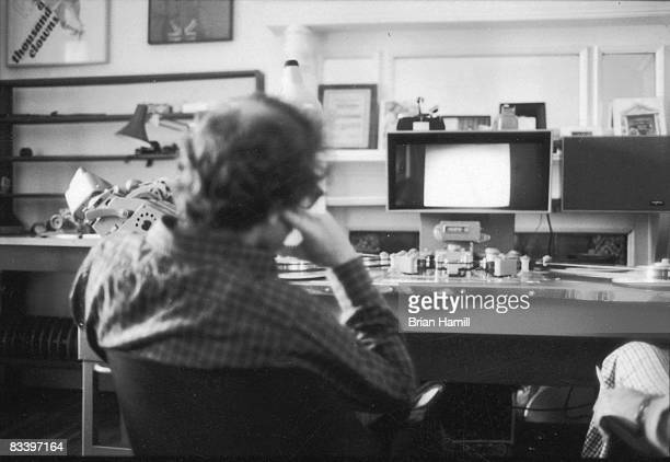 American film director Woody Allen watches footage from his movie 'Annie Hall' on an editing machine late 1970s The hand and leg of one of the film's...