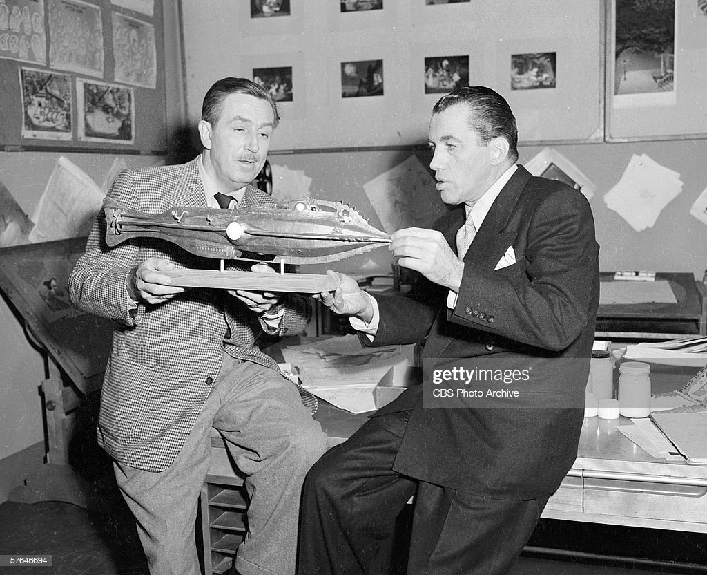American film producer and animator Walt Disney sits on a workbench in a studio and shows television personality Ed Sullivan a submarine model for...