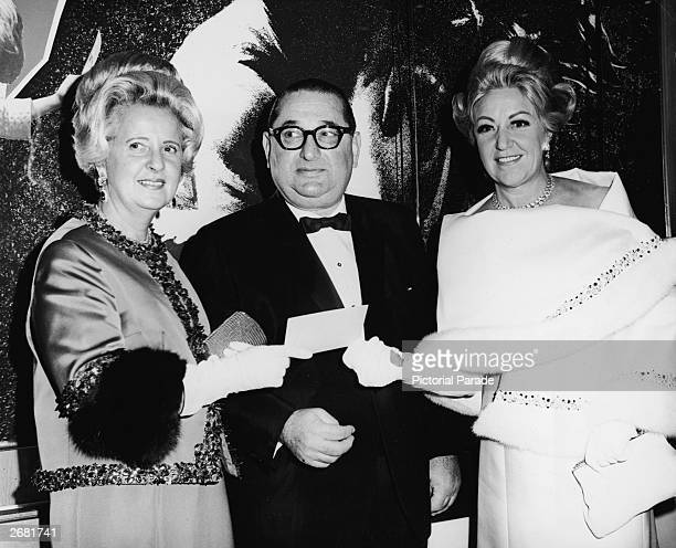 American film producer Joseph E Levine presents a check to Mrs Irving Warren of the Lila Motley Cancer Foundation as his wife looks on during the...