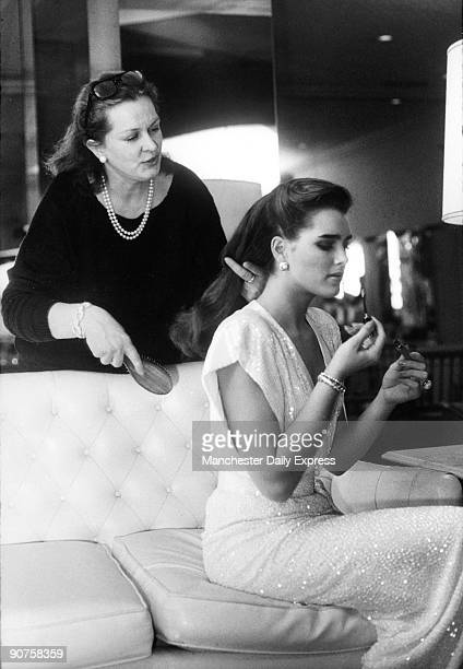 American film star Brooke Shields putting on makeup while her mother brushes her hair