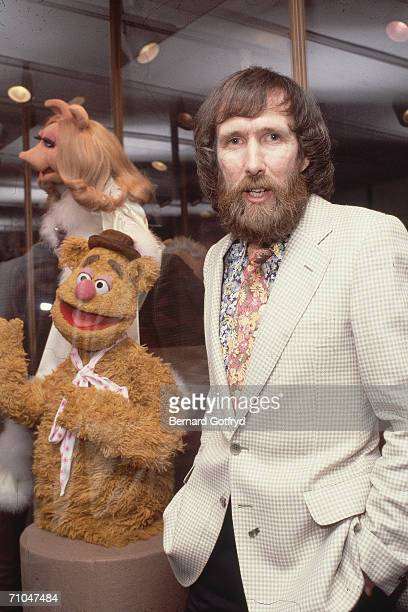 American film televison director and puppeteer Jim Henson stands with his hands in his pants pockets and poses with his muppets Fozzie Bear and Miss...