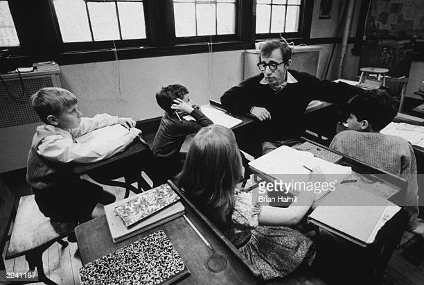 American filmmaker Woody Allen directs some young children in a classroom on the set of his film 'Annie Hall'