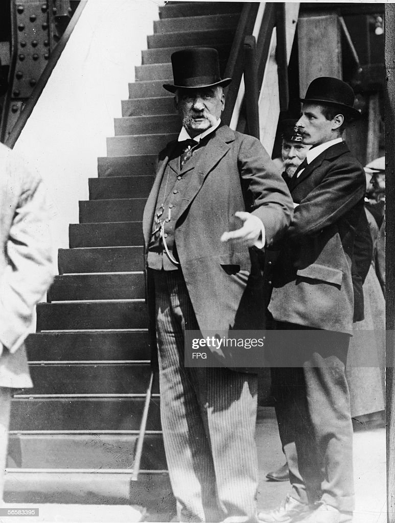 American financier John Pierpoint Morgan Sr gestures as he stands hear to a staircase early 1900s