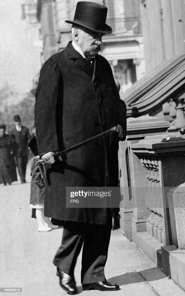 American financier John Pierpont Morgan Sr dressed in a long coat and top hat carries a walking stick as he strolls along a sidewalk early 1900s