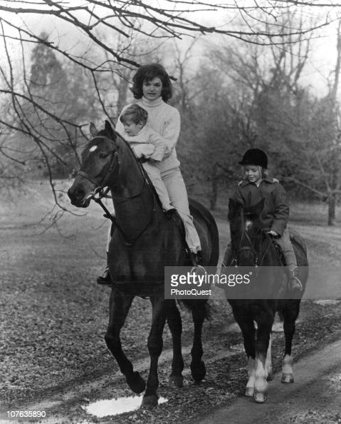 American First Lady Jacqueline Kennedy hold her son John F Kennedy Jr as they ride horses with daughter Caroline Kennedy at the Kennedy estate Glen...
