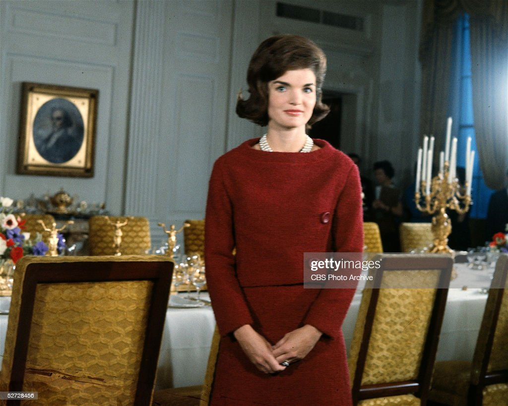 American First Lady Jacqueline Kennedy (1929 - 1994), in a red dress, stands in before a dining room table in the White House during the filming of a CBS News Special program called 'A Tour of the White House with Mrs. John F. Kennedy,' Washington DC, January 15, 1962.