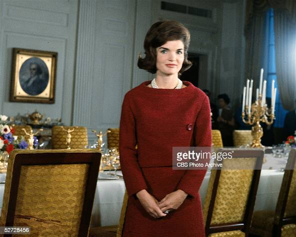 American First Lady Jacqueline Kennedy in a red dress stands in before a dining room table in the White House during the filming of a CBS News...