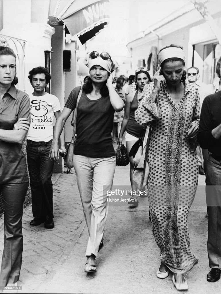 American first lady Jacqueline Kennedy Onassis (1929 - 1994) wearing a kerchief on her head walks through a busy street with the Gaines girls in Capri, Italy, early 1970s.