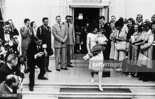 American First Lady Jacqueline Lee 'Jackie' Bouvier Kennedy holding her son John Jr at the White House North Portico May 24 while the President...