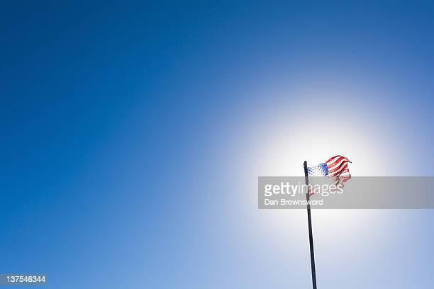 American flag against sun and blue sky