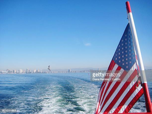 American Flag And Wake In Sea Against Clear Sky