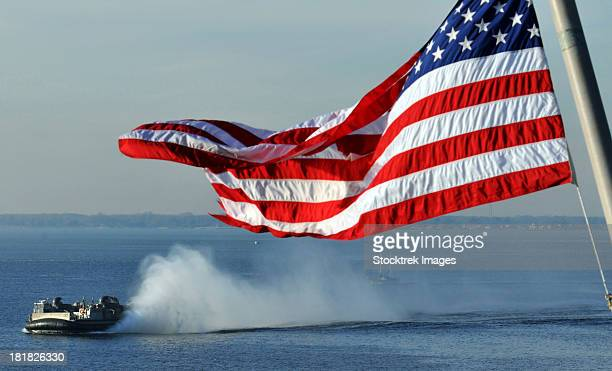 American flag blowing in the wind with a hovercraft in the background.