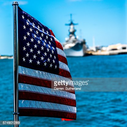 American flag blowing in the wind with navy ship in the background, Hawaii