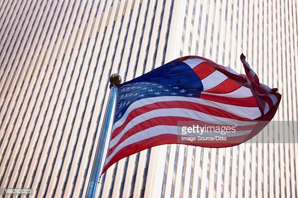 American flag flying by city skyscraper