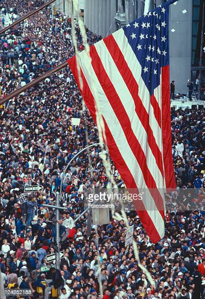 American flag flying over large crowd at tickertape parade