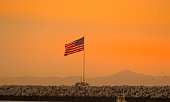 American flag flying over rocky jetty during sunset