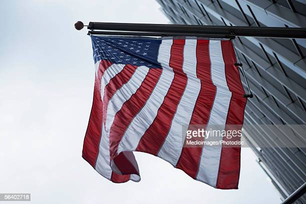 American flag hanging in front of skyscraper, New York City, NY, USA