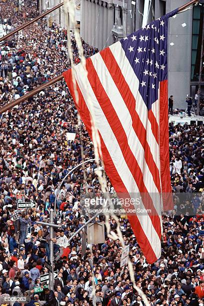 American flag hanging over crowd at ticker tape parade