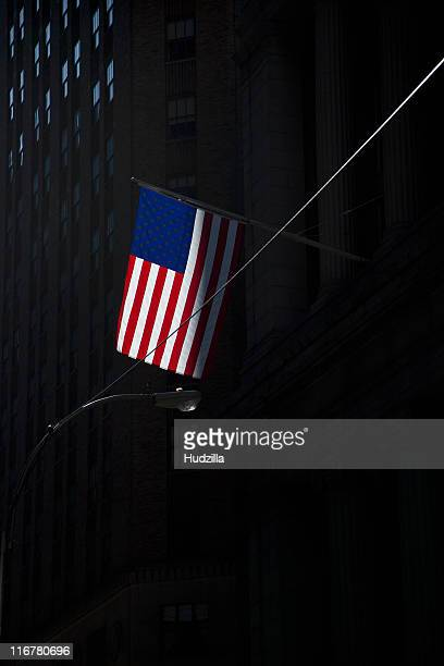 American flag on flagpole attached to shadowed tall building