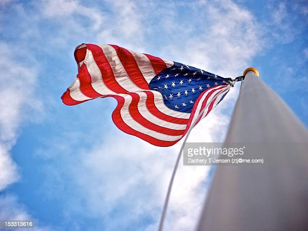 American flag on pole with clouds