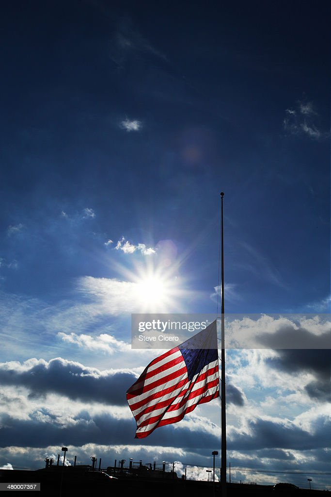 American flag silhoutted at half mast