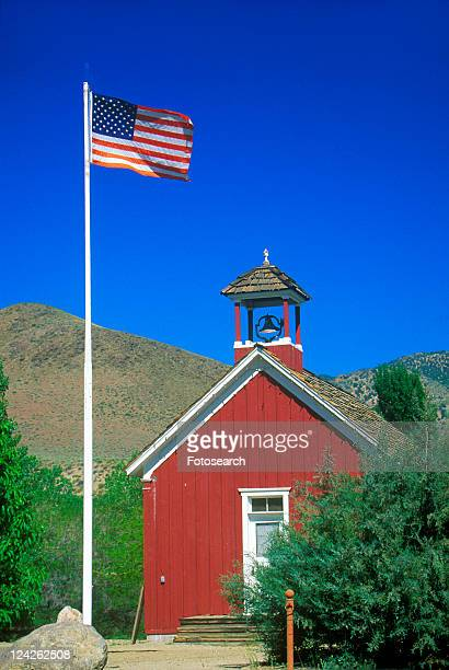 American flag waving above one room schoolhouse