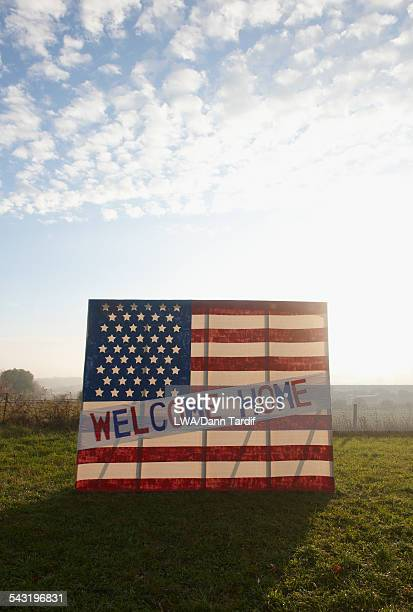 American flag with welcome home banner in field