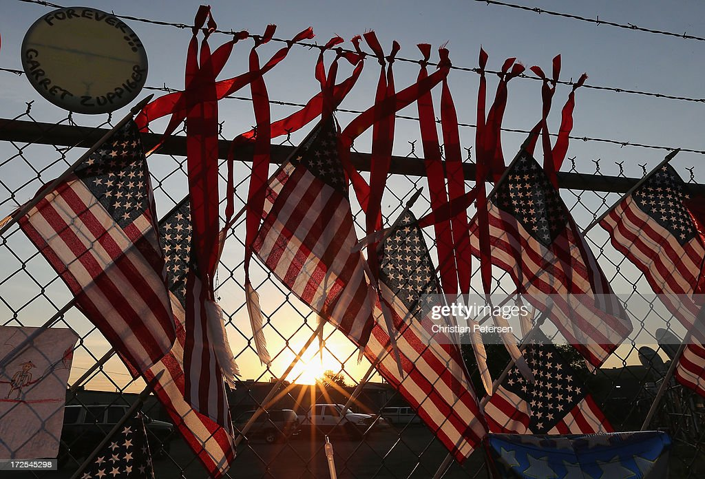 American flags and mementos adorn the outside fence of Station 7 on July 3, 2013 in Prescott, Arizona. Nineteen firefighters based out of Station 7 died battling a fast-moving wildfire near Yarnell, Arizona on June 30. Station 7 has been the home of the Granite Mountain Interagency Hotshot Crew since 2010.
