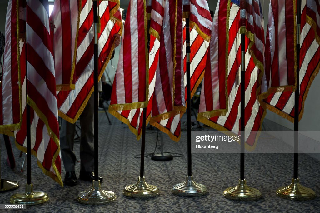 American flags are adjusted outside the Senate Judiciary Committee hearing room before the start of a confirmation hearing for Neil Gorsuch, U.S. Supreme Court nominee for U.S. President Donald Trump, not pictured, in Washington, D.C., U.S., on Monday, March 20, 2017. Gorsuch goes before a Senate committee as a heavy favorite, given Republican control, to win confirmation to a lifetime seat on the nations highest court. Photographer: Andrew Harrer/Bloomberg via Getty Images