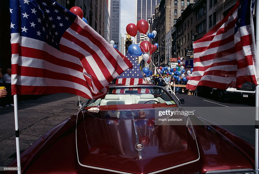 American flags are attached to the hood of a Cadillac convertible during a Labor Day celebration in New York City.