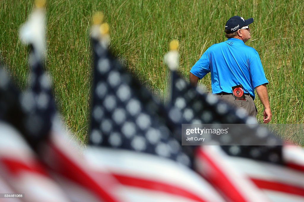 American flags blow in the wind as a fan watches a group tee off on the eighth hole during the first round 2016 Senior PGA Championship presented by KitchenAid at the Golf Club at Harbor Shores on May 26, 2016 in Benton Harbor, Michigan.