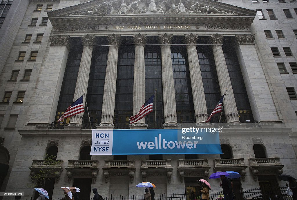 American flags fly as pedestrians carry umbrellas while walking past the New York Stock Exchange (NYSE) in New York, U.S., on Friday, May 6, 2016. U.S. stocks retreated a fourth day, with the S&P 500 poised for its first back-to-back weekly drop since February, after the smallest jobs gain in seven months raised doubts about the strength of the worlds largest economy. Photographer: Victor J. Blue/Bloomberg via Getty Images