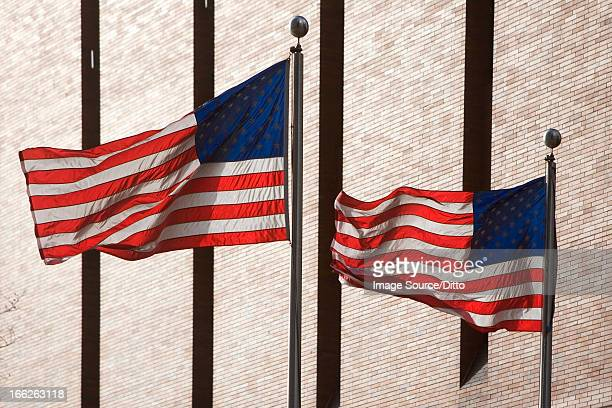 American flags flying by skyscraper